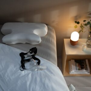 An image of a CPAPA travel pillow on a bed with a CPAP mask placed in front. The room is sofely lit inviting you to relax and sleep well.