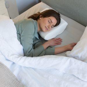 A lady lying on her side on a Putnams foam pillow