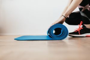 An image of someone rolling up a yoga/pilates mat to demonstrate being demotivated and leaving the class